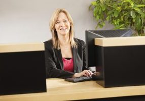 A happy, smiling Caucasian woman bank teller working with a computer at a retail banking counter. The professional businesswoman sits behind an office building bank window, well-dressed in her financial service occupation, looking at the camera. Photographed from the customer side of the counter, in vertical format with copy space.